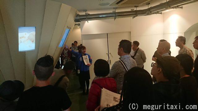 オリオンハッピーパーク工場見学を受けている見学者とガイド