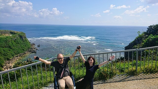 宮城島果報バンタで万歳する車椅子ユーザーと美人奥様