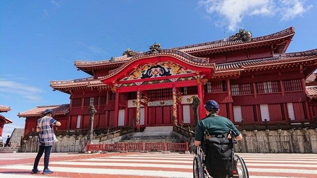 首里城御庭から正殿をながめる車椅子ユーザー
