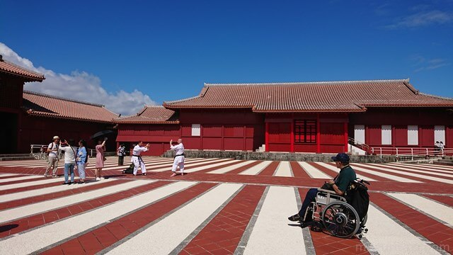 首里城御庭で空手の型を決める外人を見つめる車椅子ユーザー