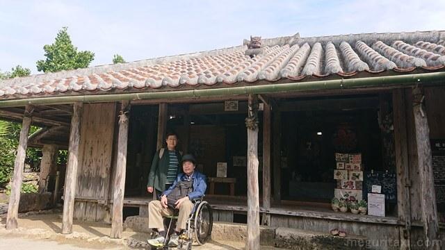 琉球村内の花城家前で写る車椅子ユーザー