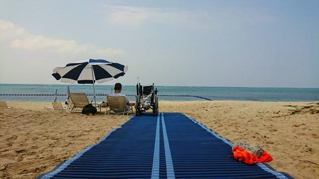 ホテルモントレ沖縄のビーチ内に車椅子通行が簡単なモビマットを活用してくつろぐ車椅子ユーザー